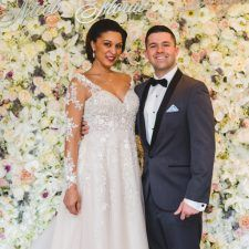 A Van Cleve Bride and Sagets Formal Wear Groom in front of the Flower Wall by Nicol Floral Designs