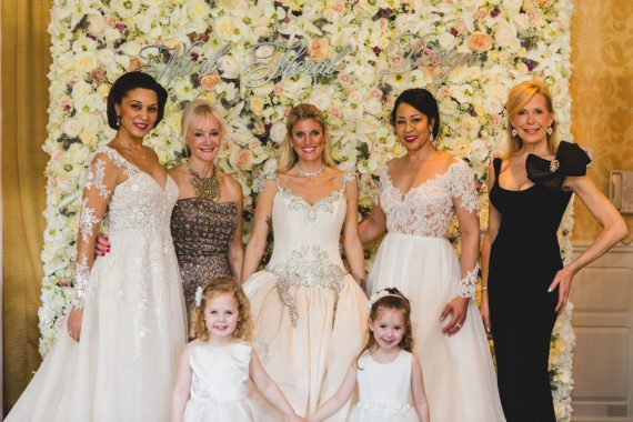 Van Cleve Brides and Flower Girls posing in front of the Flower Wall by Nicol Floral Designs